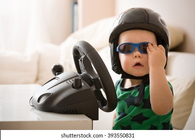 Cute little kid boy in a helmet playing with Computer steering wheel. Future driver. Getting ready for professional driving. Funny toddler boy indoors. Boy and a car.