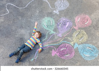 Cute little kid boy playing and flying with colorful balloons picture drawing with chalk. Creative leisure for children outdoors in summer, celebrating birthday