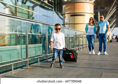 Cute little kid boy with suitcase on international airport. Mother and son on background, happy family waiting for flight and going on vacations.