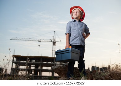 cute little kid in builder helmet with toolbox in hand on standing construction site