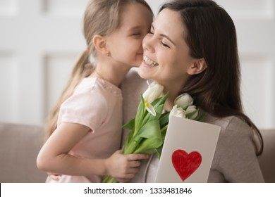 Cute little kid daughter holding spring flowers presenting greeting card congratulating happy mom with mothers day, preschool child girl embracing kiss mum make surprise to smiling mommy for birthday