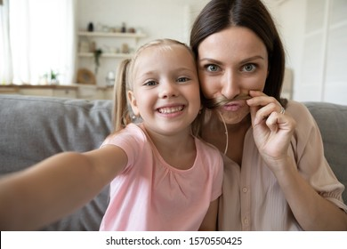 Cute little kid daughter and young mother funny moustache face taking family picture look at mobile camera, happy parent mum having fun with child girl make selfie together at home, phone cam view
