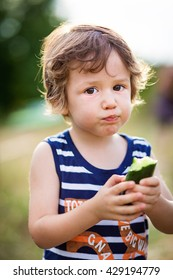 Cute little kid eating a cucumber in the garden. Kids eat vegetables outdoors. Healthy snack for children.