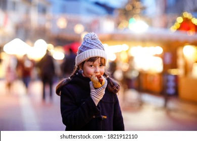 Cute little kid girl having fun on traditional Christmas market during strong snowfall. Happy child eating traditional curry sausage called wurst. schoolgirl standing by illuminated xmas tree.