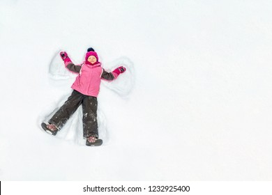Cute little kid girl in warm ski sport suit making snow angel outdoors. Kid having fun lying on snowdrift after snow storm in winter. Children outdoor activities. Winter vacation and holidays