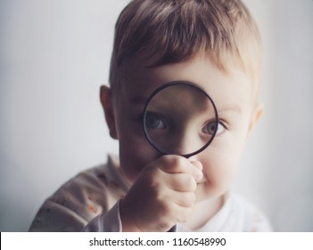 cute little kid with a magnifying glass.  smiling child looking through a magnifying glass