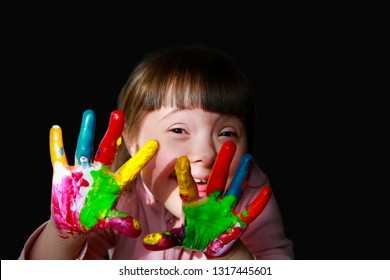 Cute little kid with painted hands isolated on the black