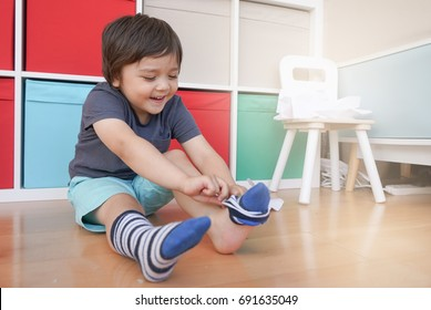 Cute little kid sitting next to tablet and learning how to put the socks on by him self, Happy Toddler boy pulling his socks to his knee , Child development concept