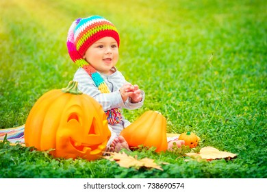 Cute little kid sitting on green grass field wearing funny colorful hat and playing with pumpkins with smiling carved faces, happy Halloween holiday