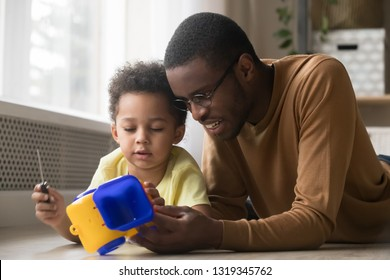 Cute little kid son holding screwdriver repairing toy car playing game with black dad baby sitter lying on warm floor, african family father and toddler child boy having fun fixing truck at home