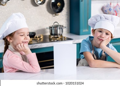 cute little kids in chef hats sitting with blank card in kitchen