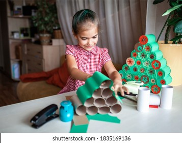 Cute little kids making handmade advent calendar with toilet paper rolls at home. Glue, colored paper, cut punch to hide sweets and candies in rolls. Seasonal activity for kids, zero waste holidays
