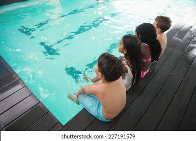 Cute little kids sitting poolside at the leisure center