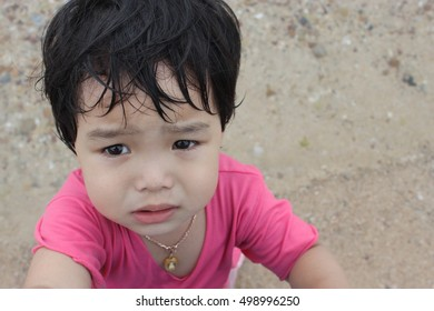 Cute little kids wearing pink shirt are crying and pleading eyes plead, while strolling on the beach.