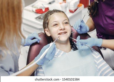 Cute little lady in the dentist's office. Woman in a uniform. Doctor with a patient