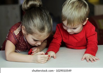 Cute little lady and her smaller brother spending time at home, girl painting nails to her brother, boy looking at this with interest, family relations concept, indoor lifestyle
