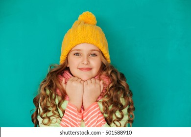 937b86a9f3a Cute little lady wearing yellow woolen cap and warm scarf against turquoise  background