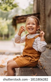 Cute little laughing girl with beautiful smile and blue eyes sitting on wooden terrace floor next to house. Close up portrait of happy three years old child with two blonde pigtails. Nature background