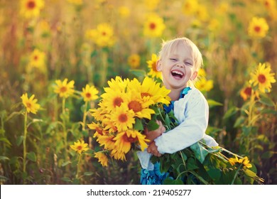 A cute little laughing girl in the field of sunflowers holding a huge bunch of flowers in a sunny summer evening.