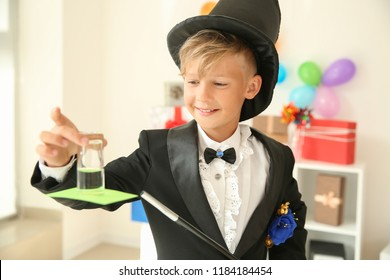 Cute little magician showing trick indoors
