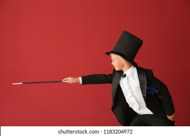 Cute little magician showing tricks on color background