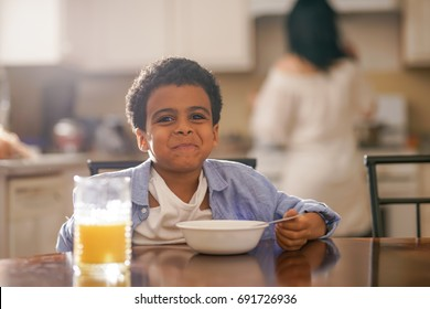 cute little mixed race boy making funny face with mother in background at breakfast