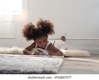 Cute little mixed race girl lying down on the floor with carpet, drawing with colorpencils. Concentration, homeschool and education concept.
