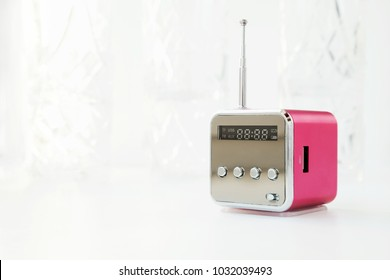Cute little modern radio with antenna on a white background. New pink cube radio receiver with copy space. Wireless hi-tech electronic mass media equipment