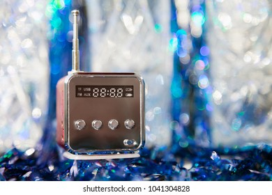 Cute little modern radio with antenna on a blue sparkling background. New reflecting cube radio receiver with copy space. Wireless hi-tech electronic mass media equipment