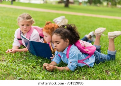 cute little multiethnic schoolgirls reading book together on grass