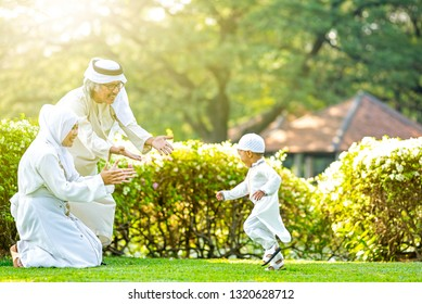 Cute little Muslim boy running to his  family for give a hug in park on grass field. Muslim family concept.