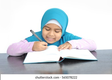 Cute little muslim girl doing homework, reading a book,writing. Preschooler with books at home.Learn to write and read. Creative toddler