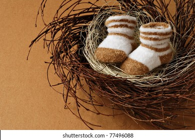 Cute little newborn baby booties in nest on brown paper background with copy space.  Motherhood concept.