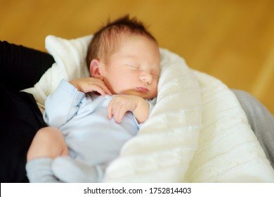 Cute little newborn baby boy sleeping in his mothers arms. Portrait of tiny new baby at home. Adorable son being held by his mommy. New bundle of joy.