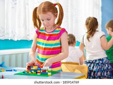 Cute little orange haired girl playing at kindergarten