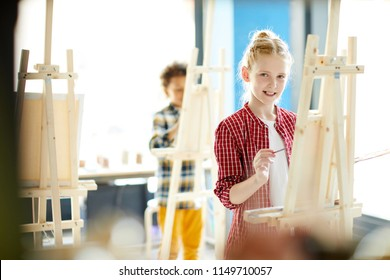 Cute little painter with palette and paintbrush standing in front of easel and painting in studio of arts