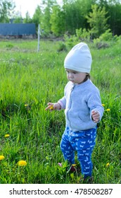 Cute little playful girl in blue pants, gray jacket and white hat playing on meadow in the field of grass and dandelions flowers in the countryside, rustic style concept photo