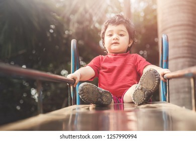 Cute little playing slide at the playground, looking down with surprised face, Active child playing outdoors in the sunny day