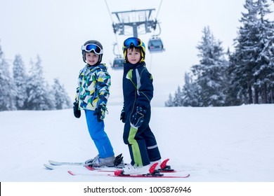 Cute little preschool children, boy brothers in blue jackets, skiing happily on a sunny day in Als