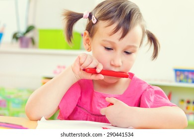 Cute little preschool girl drawing with colorful pencils