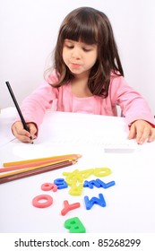 Cute little preschool girl playing with letters and drawing with pencils on white