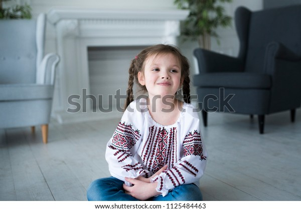 cute little pre-school girl smiling with white teeth sitting on the white wooden floor in modern interior grey color, traditional embroidered suit on