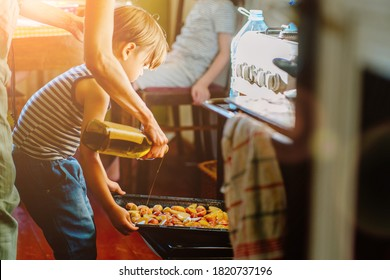 Cute little preschooler boy in striped t-shirt help his mother at kitchen. Cook at home. Young woman pouring oil at a baking tray before oven. Her son helping hold. Family cooking dinner together