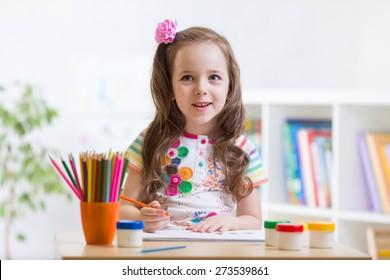 Cute little preschooler child girl drawing at house