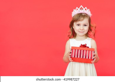 Cute little preschooler girl christmas portrait, isolated on red. Child girl wearing crown and white dress holding a red gift box  isolated over red background