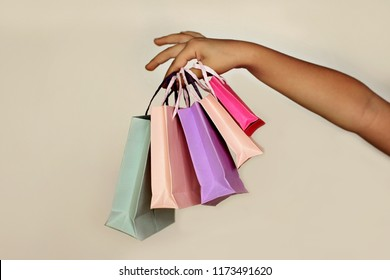 Cute little preschooler girl holding a few different colorful shopping bags over white background. Sale, gifts, holidays. Beauty and fashion concept