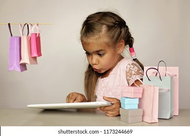 Cute little preschooler girl shopping online using her tablet over white background, she is surrounded with different colorful shopping bags. Sale, gifts, holidays. Beauty and fashion concept