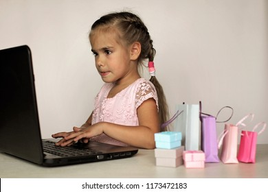 Cute little preschooler girl shopping online using her laptop over white background, she is surrounded with different colorful shopping bags. Sale, gifts, holidays. Beauty and fashion concept