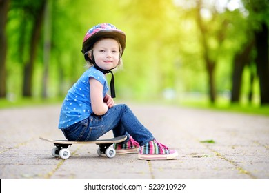 Cute little preteen girl wearing helmet sitting on a skateboard in beautiful summer park