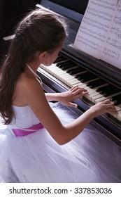 Cute little princess girl plays piano in the studio